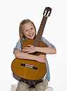 Girl embracing guitar against white background, smiling, portrait - WWF001899
