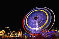 Germany, Bavaria, Munich, View of illuminated amusement ride in speed at night - FO003332