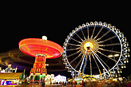 Germany, Bavaria, Munich, View of illuminated chairoplane and ferris wheel at night - FOF003337