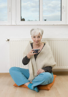 Germany, Duesseldorf, Woman drinking tea near heater at home, smiling, portrait - UKF000218