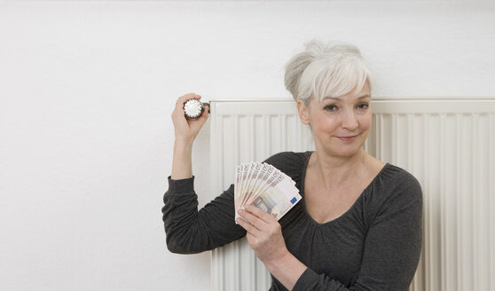 Germany, Duesseldorf, Woman holding banknotes and adjusting heater at home, smiling, portrait - UKF000220