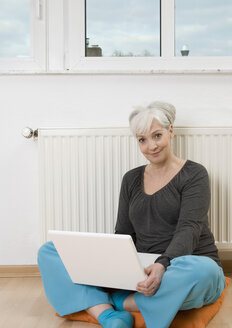 Germany, Duesseldorf, Woman using laptop near heater at home, smiling, portrait - UKF000197
