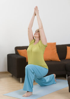 Germany, Duesseldorf, Woman doing yoga near sofa at home - UKF000191