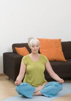 Germany, Duesseldorf, Woman doing yoga near sofa at home - UKF000187