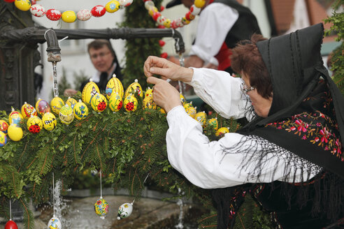 Germany, Bavaria, Franconia, Franconian Switzerland, Muggendorf, Woman in traditional costume decorating easter well - SIE001425