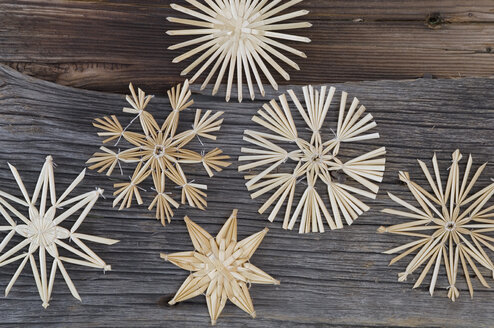 Close up of straw star for christmas decoration on tree trunk - ASF004348
