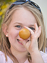 Germany, Bavaria, Close up of girl joking with easter eggs, smiling, portrait - LFF000255