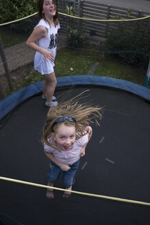 Germany, Bavaria, Two girls jumping on trampoline - LF000258