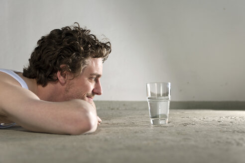 Mid adult man lying on floor and staring at glass of water - DBF000094