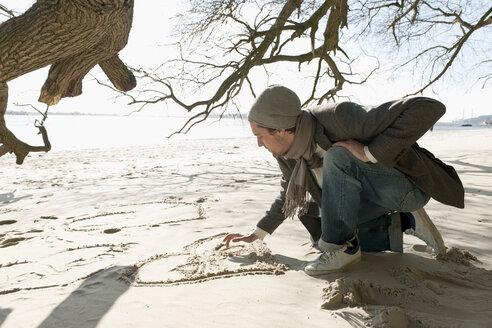 Germany, Hamburg, Man writing on sand near Elbe riverside - DBF000100