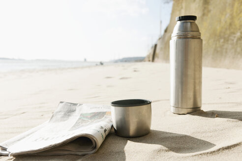 Germany, Hamburg, Close up of newspaper and thermos flask at beach near Elbe riverside - DBF000120