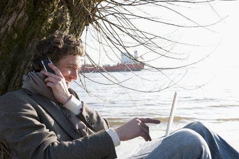 Germany, Hamburg, Man using laptop and cell phone near Elbe riverside with container ship in background - DBF000125