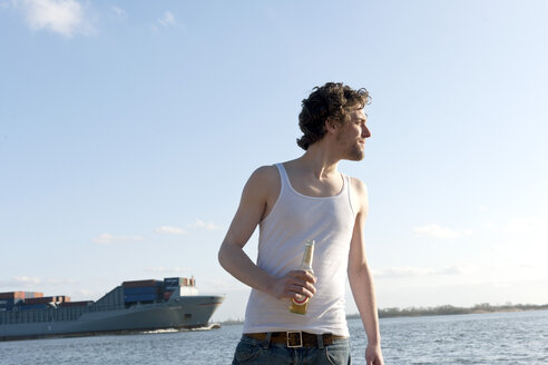 Germany, Hamburg, Man with beer bottle near Elbe riverside and container ship in background - DBF000131
