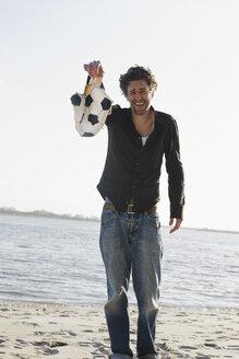 Germany, Hamburg, Man holding torn football near Elbe riverside - DBF000134