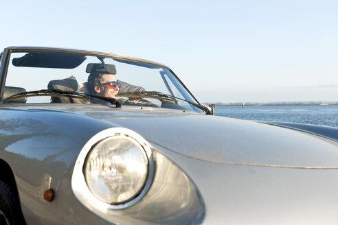Germany, Hamburg, Man sitting in classic cabriolet car near Elbe riverside - DBF000136
