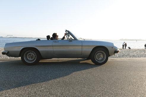 Germany, Hamburg, Man sitting in classic cabriolet car near Elbe riverside - DBF000139