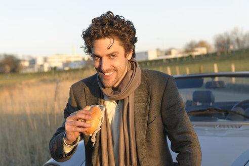 Germany, Hamburg, Man eating fish sandwich beside classic cabriolet car - DBF000103