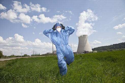 Germany, Bavaria, Unterahrain, Man with protective workwear running in field at AKW Isar - MAEF003268