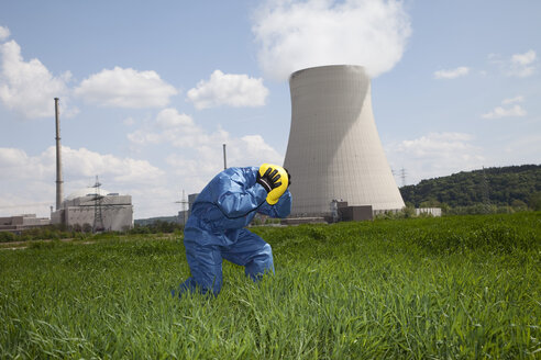Germany, Bavaria, Unterahrain, Man with protective workwear covering his ears in field at AKW Isar - MAEF003280