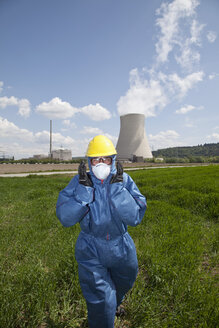 Germany, Bavaria, Unterahrain, Man with protective workwear walking in field at AKW Isar - MAEF003286