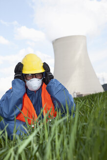 Germany, Bavaria, Unterahrain, Man with protective workwear and covering ears in field at AKW Isar - MAEF003295