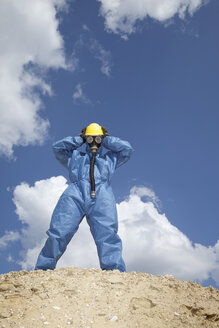 Germany, Bavaria, Man in protective workwear standing on top of sand dune - MAEF003310