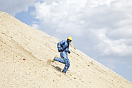 Germany, Bavaria, Man in protective workwear running on slope of sand dune - MAEF003313