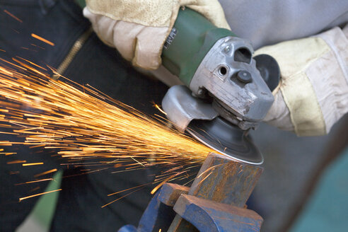 Close up of man sharpening piece of iron with angle grinder - TSF000258