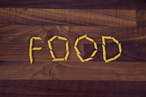 Close up of word food written with penne on wooden background - TSF000255