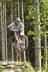 Germany, Bavaria, Chiemgau, Samerberg, Man doing stunt with mountain bike - FFF001225