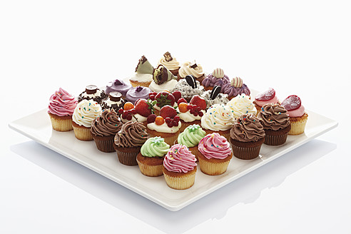 Variety of buttercream cupcakes on tray against white background - CSF014994