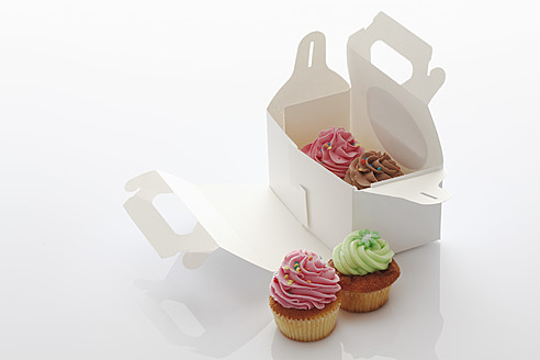 Close up of strawberry, chocolate and woodruff buttercream cupcakes in box against white background - CSF014991