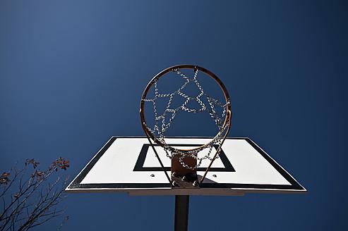Germany, North Rhine-Westphalia, Düsseldorf, Empty basketball hoop against blue sky - KJF000100