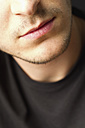 Lips of young man with stubble against black background, close up - MBEF000109