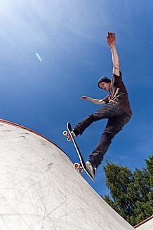 Belgium, Flemalle, Young man skate boarding in skatepark - KJF000107
