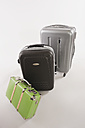 Variety of suitcases and luggages in a row against white background - WESTF016723