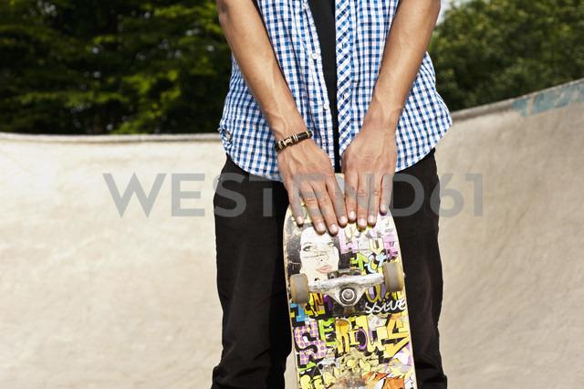 Germany, NRW, Duesseldorf, Man holding skateboard at public skatepark - KJF000110