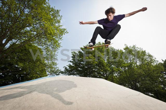 Germany, NRW, Duesseldorf, Man skateboarding at public skatepark - KJF000114