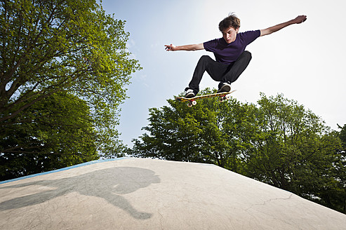 Germany, NRW, Duesseldorf, Man skateboarding at public skatepark - KJF000114