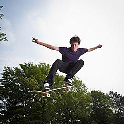 Germany, NRW, Duesseldorf, Man skateboarding at public skatepark - KJF000115