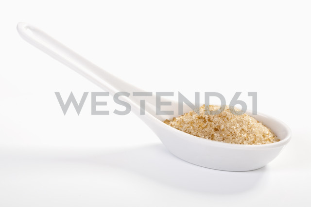 Brown sugar in porcelan spoon on white background - TSF000292