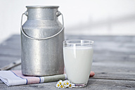 Germany, Close up of milk churn and milk glass on wooden table - MAEF003351