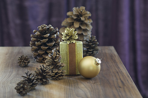 Close up of pine cones and golden christmas bauble with present - ASF004369