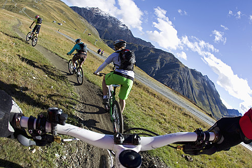 Italy, Livigno, View of woman and man riding mountain bike downhill - FFF001174