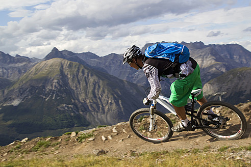 Italy, Livigno, View of man riding mountain bike downhill - FFF001192