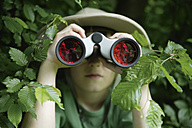 Germany, Bavaria, Close up of boy looking through binocular in forest - TCF001546