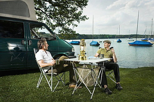 Germany, Bavaria, Woerthsee, Two men having drinks and talking near lakeshore while camping - RNF000624