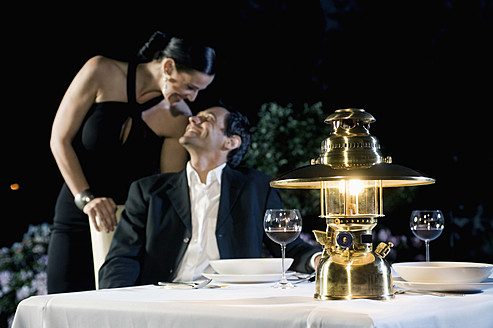 Germany, Bavaria, Couple romancing while candlelight dinner - RNF000635