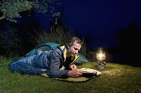 Germany, Bavaria, Ammersee, Man reading book near lakeshore while camping at night - RNF000615