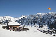 Austria, Vorarlberg, Lech am Arlberg, People skiing and paragliding near ski hut in winter - WD000968